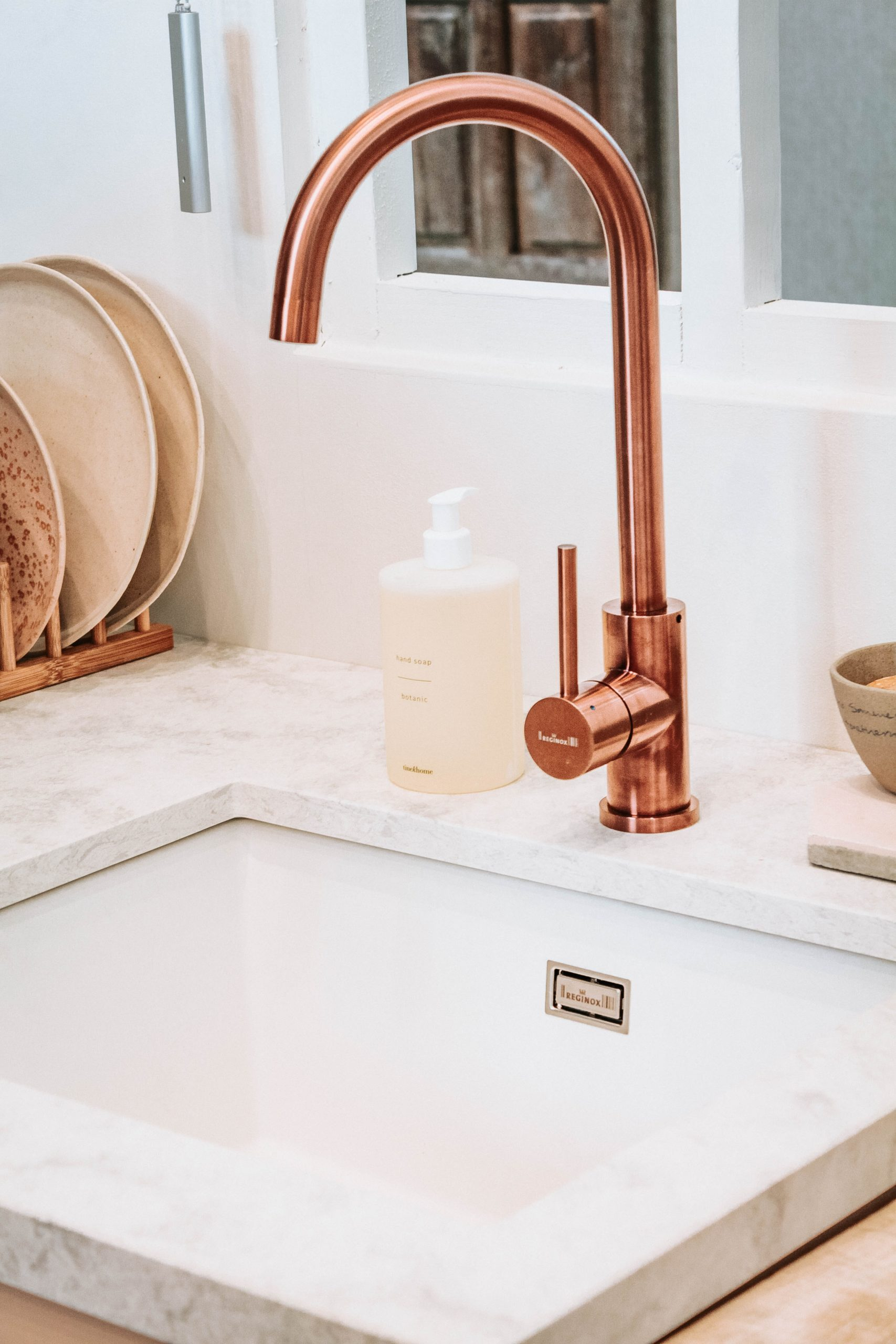 copper disc faucet in a white sink