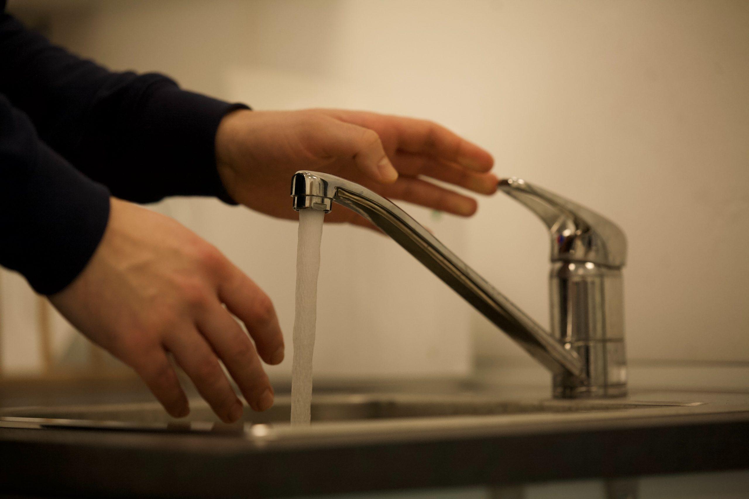 man turning off kitchen tap