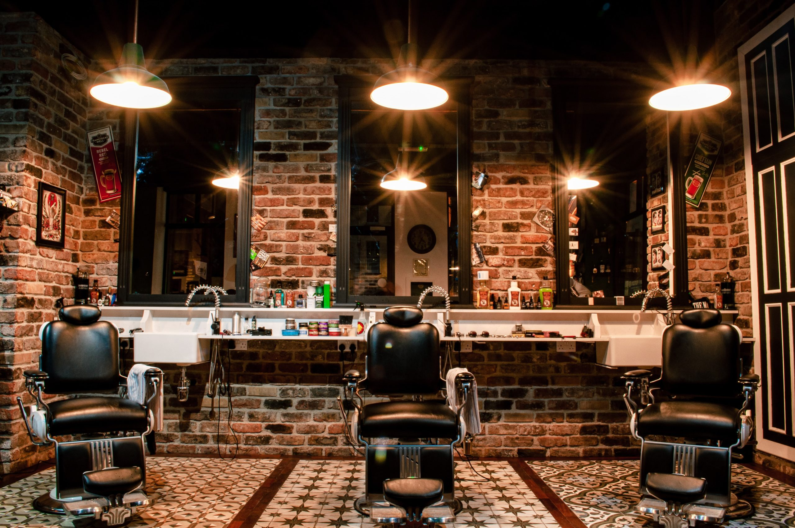 masculine barber shop with red mixed brick walls, mirrors, dim lights and tiled floor