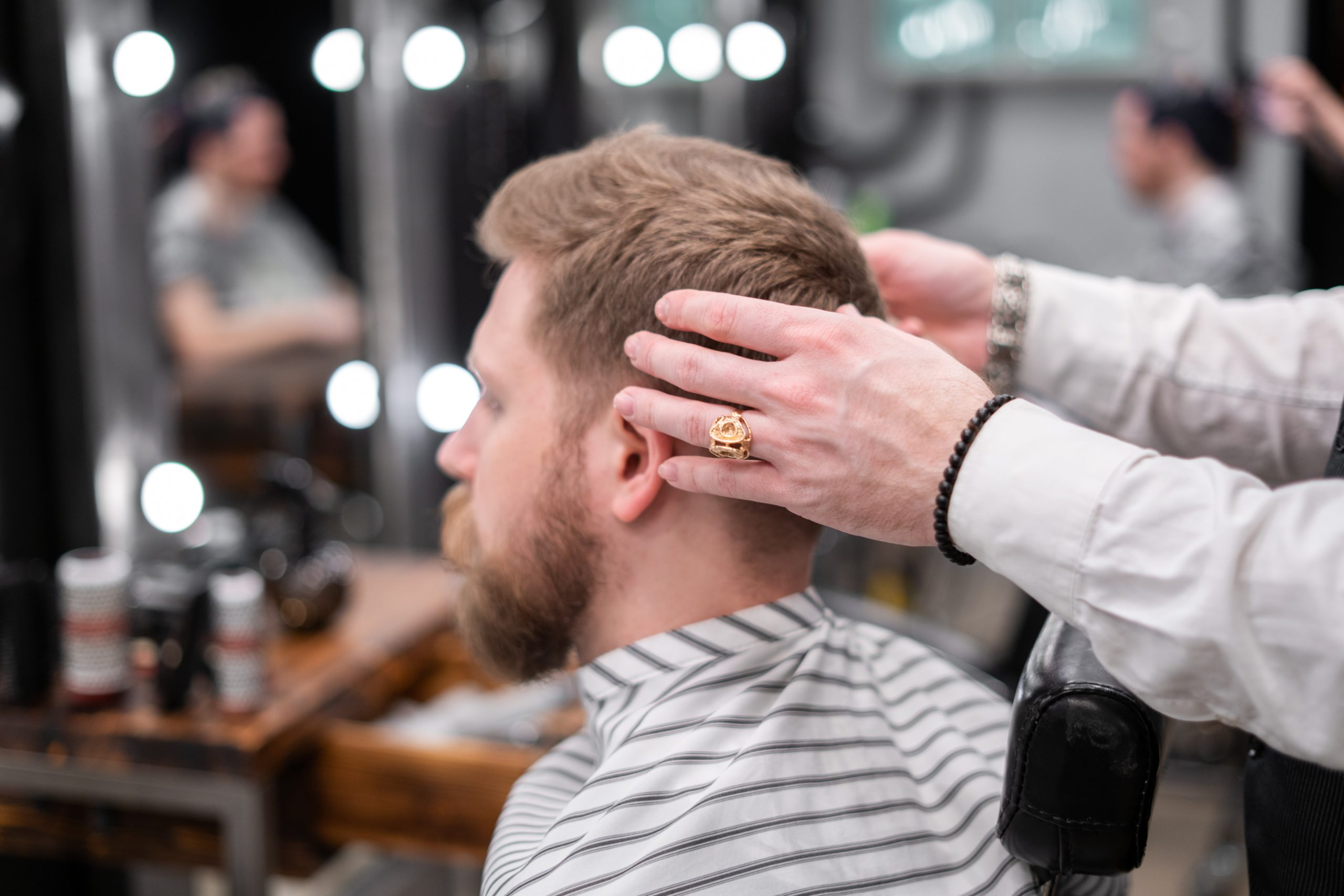 man with blonde hair and beard getting haircut