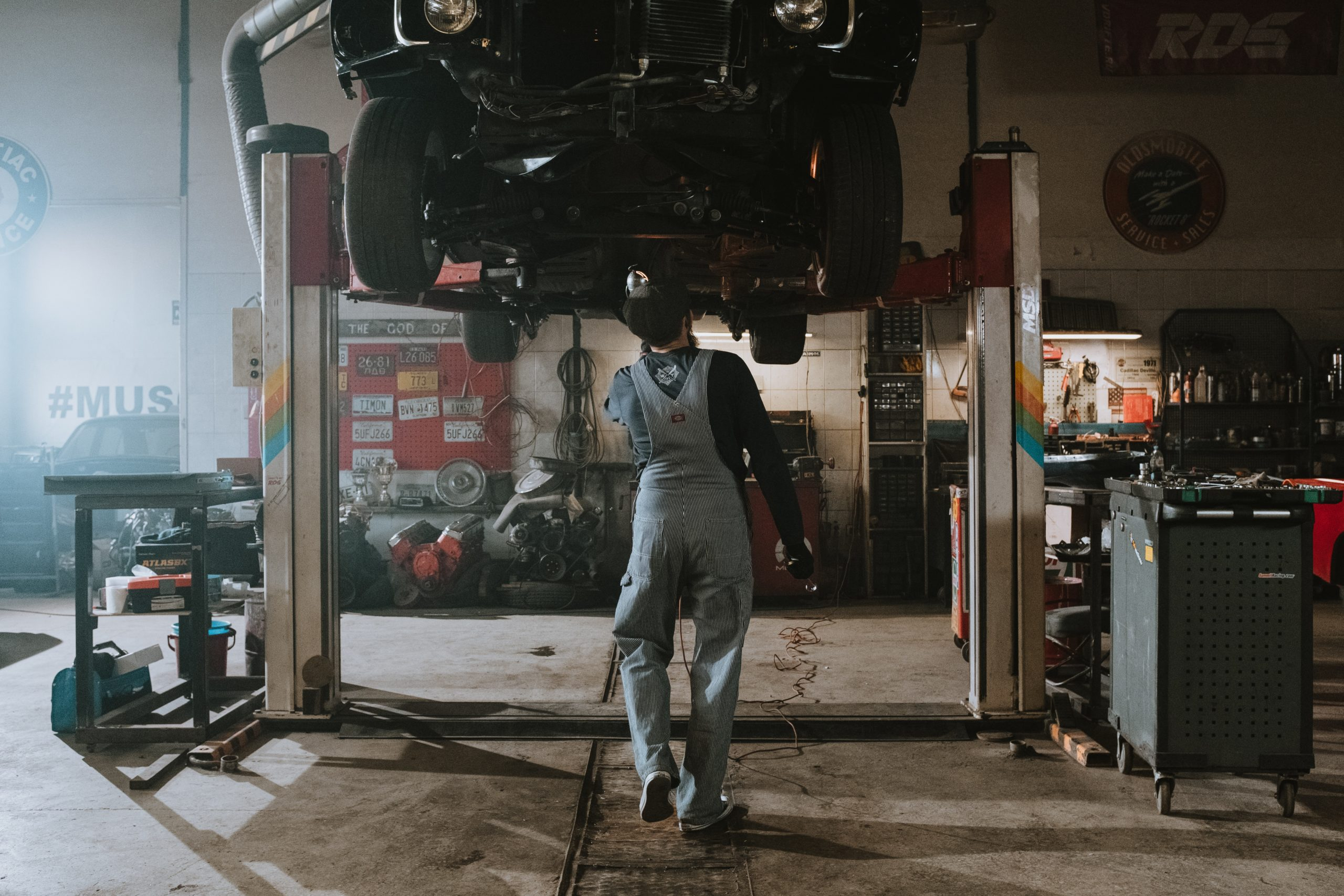 mechanic walking under a lifted car in the shop