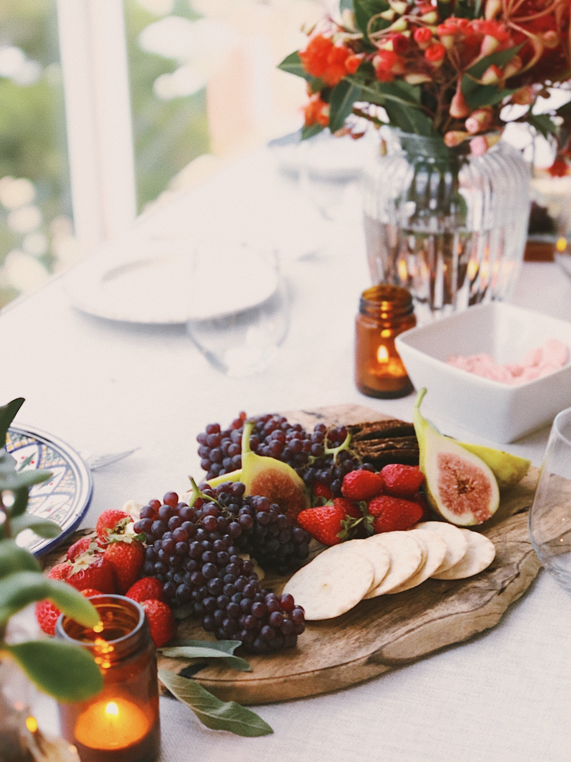 fancy fruit filled charcuterie board on table with a white table cloth.