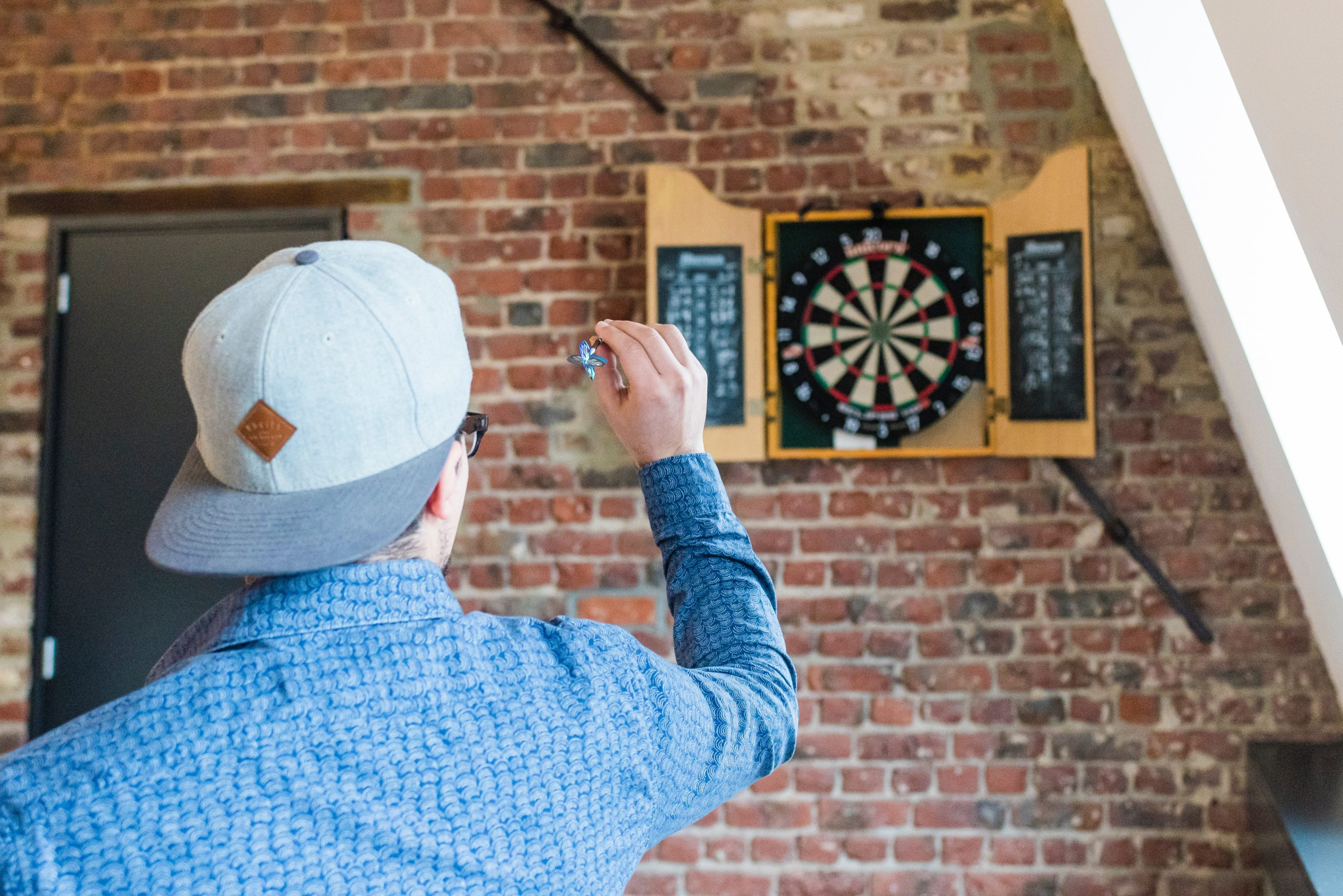 man with hat on backwards and a blue shirt tossing a dart at a dartboard on a brick wall