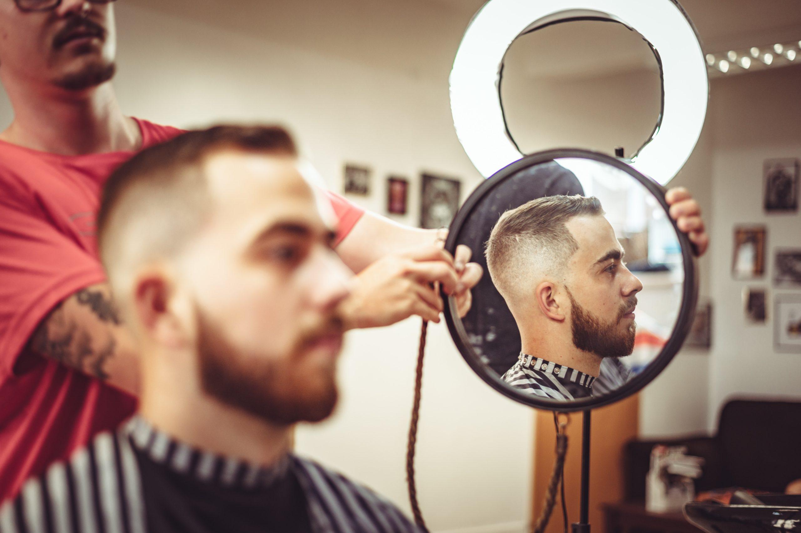 man being shown haircut through mirror