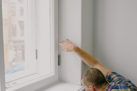 white man wearing checkered shirt, repairing window sill in white room