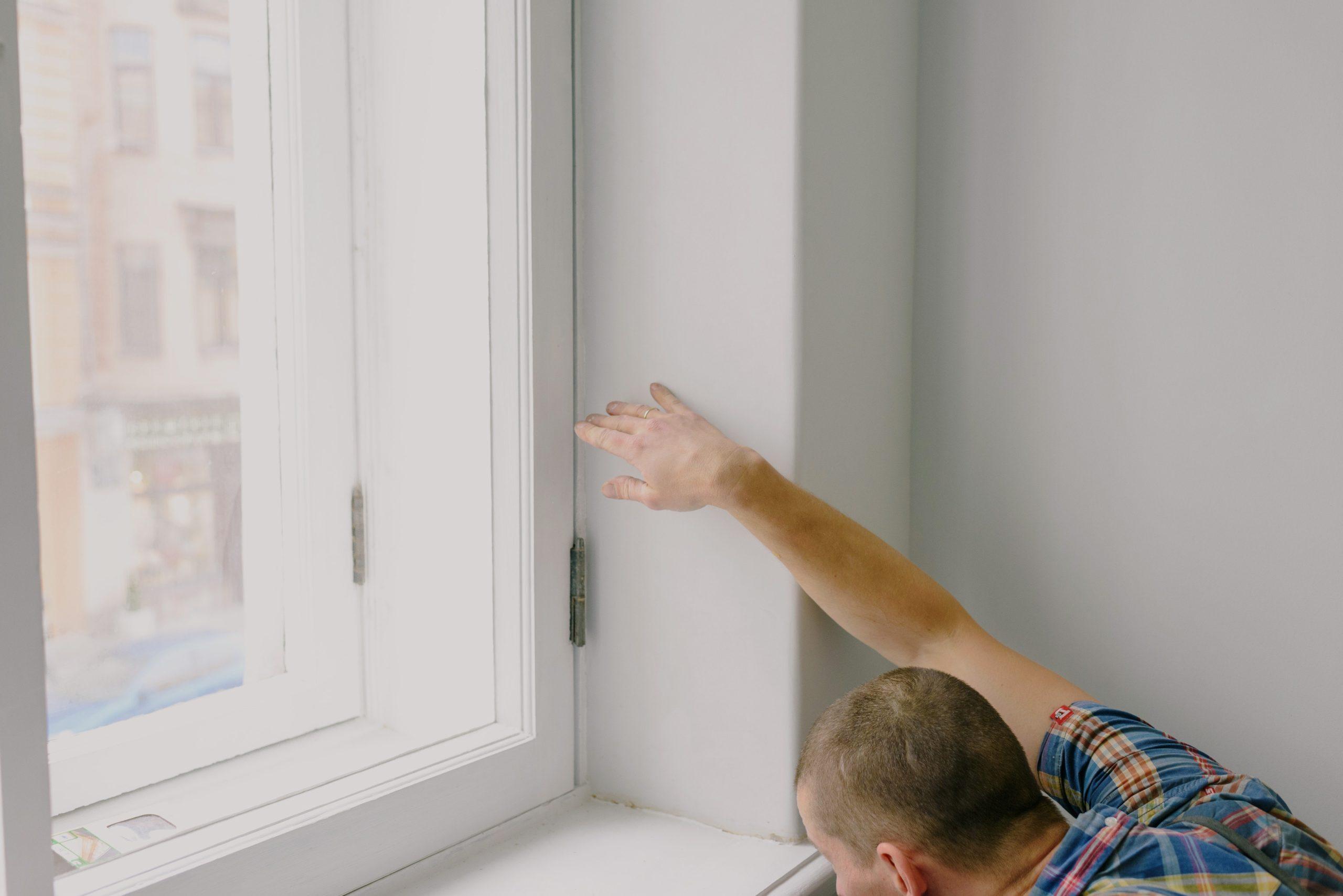 white man wearing checkered shirt, repairing window sill in white room