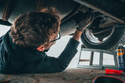 Mechanic performing repairs under a lifted car