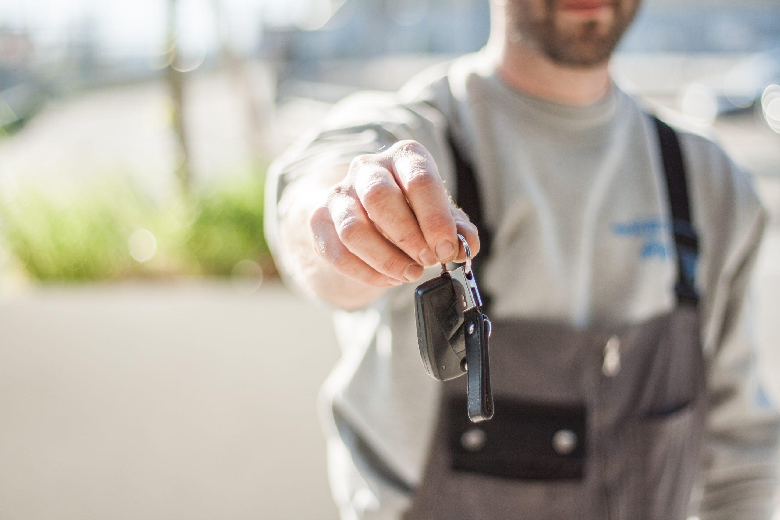 mechanic holding keys IN front of him outside