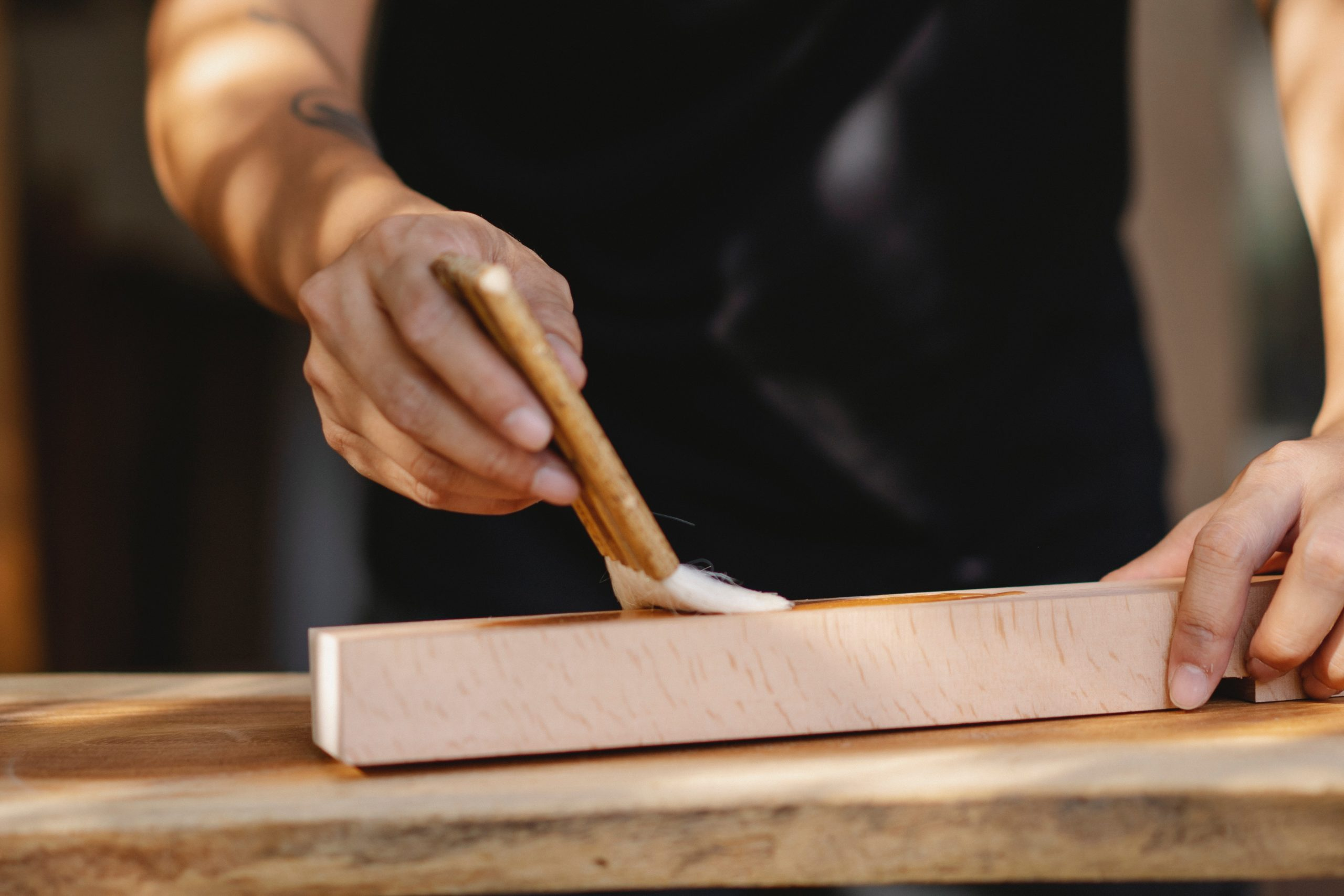 man applying Lacquer iwth a paint brush on a wood surface outside