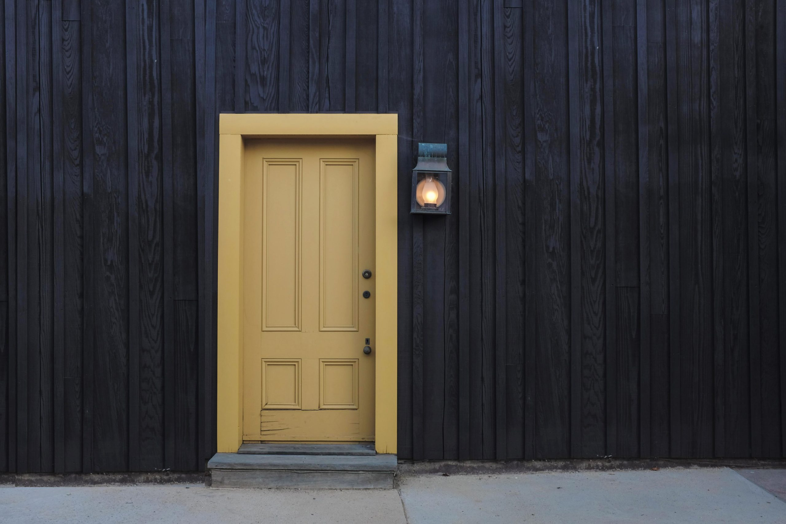 Yellow exterior front door on a dark siding building with the exterior light turned on