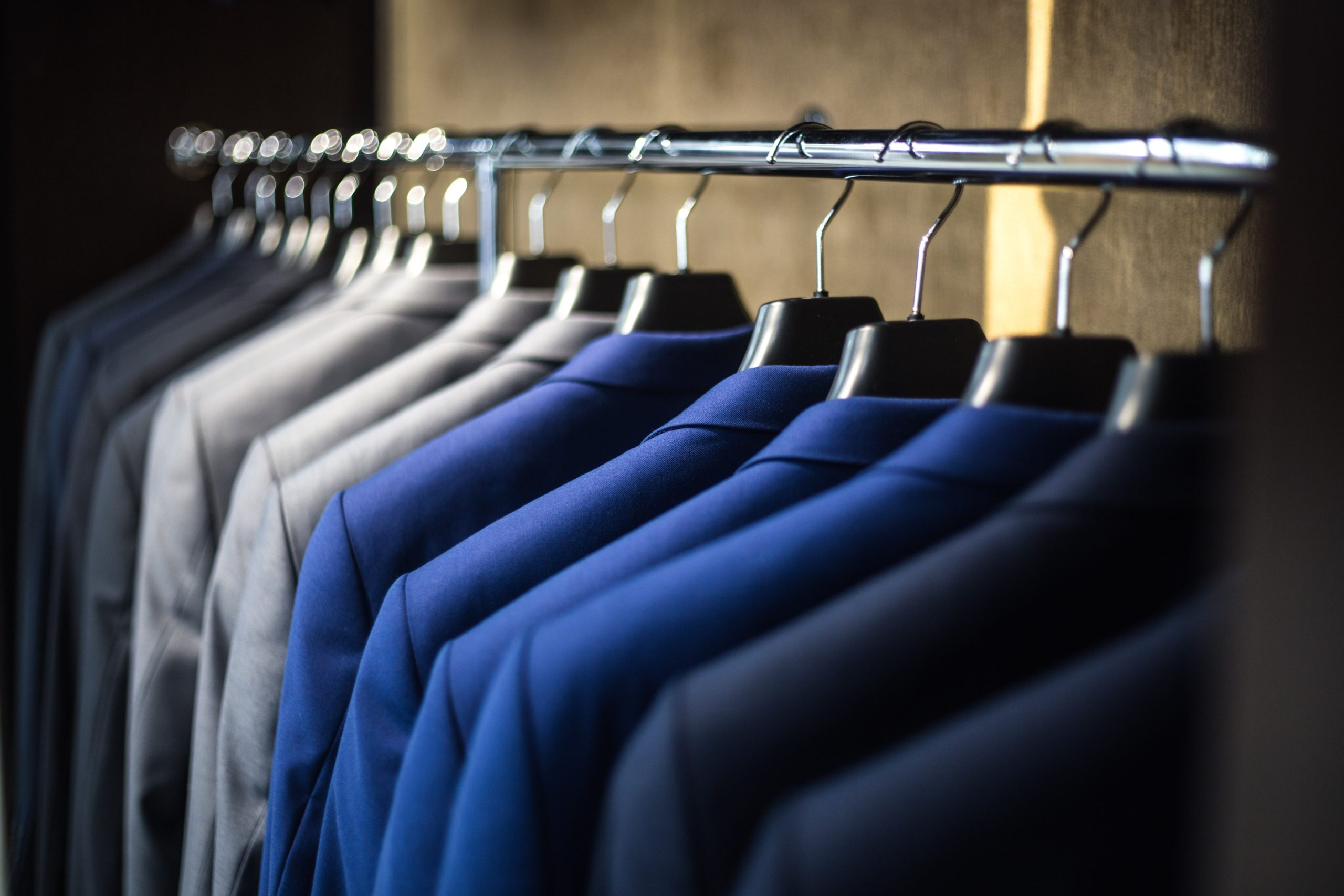 Row of blue and light gray suits hanging on a rack