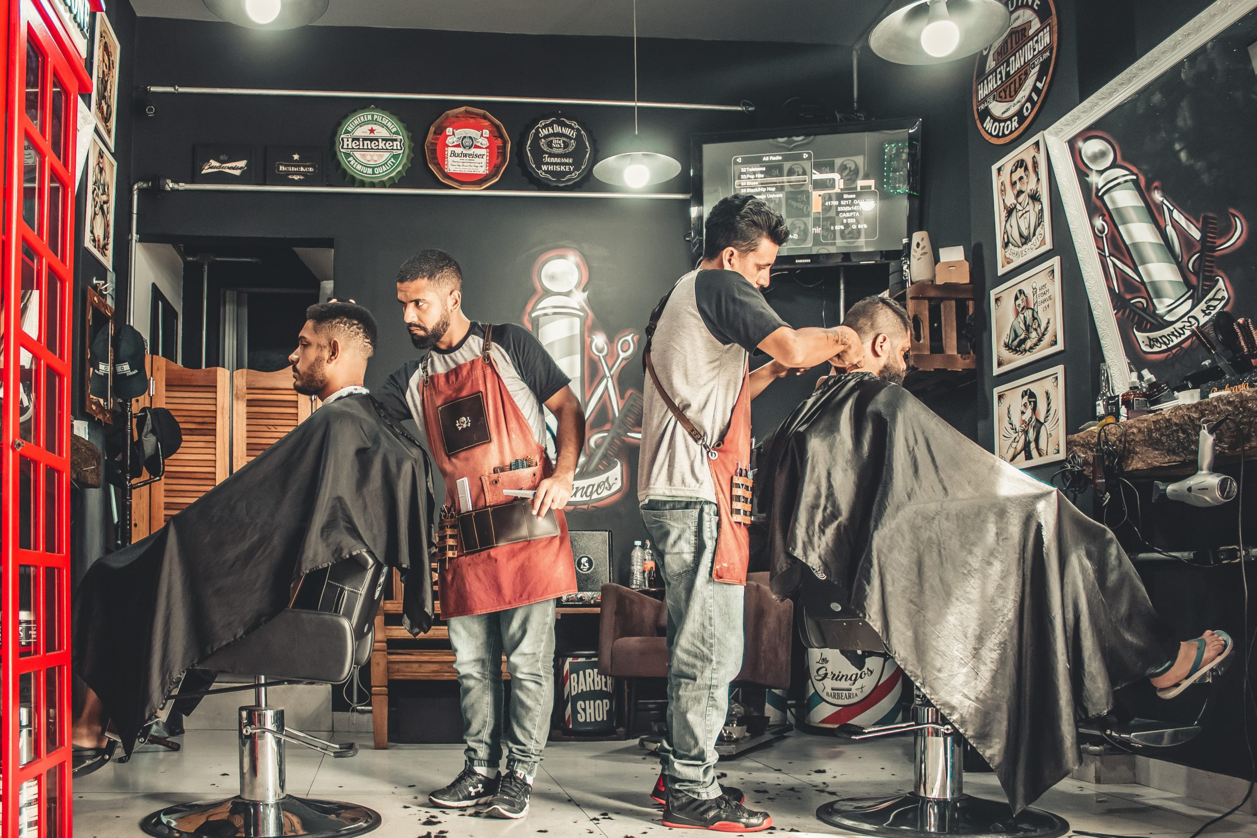 two barbers giving haircuts to two men