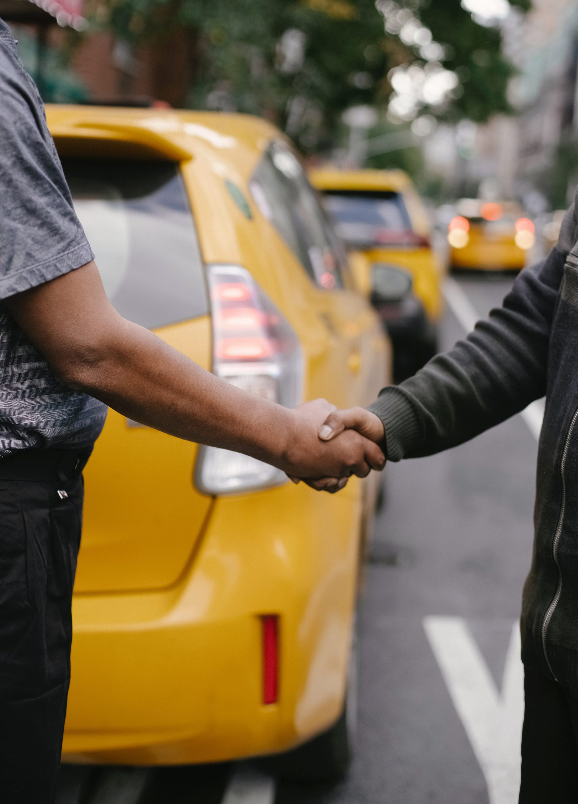 2 men shaking hands on a street with yellow parked cars