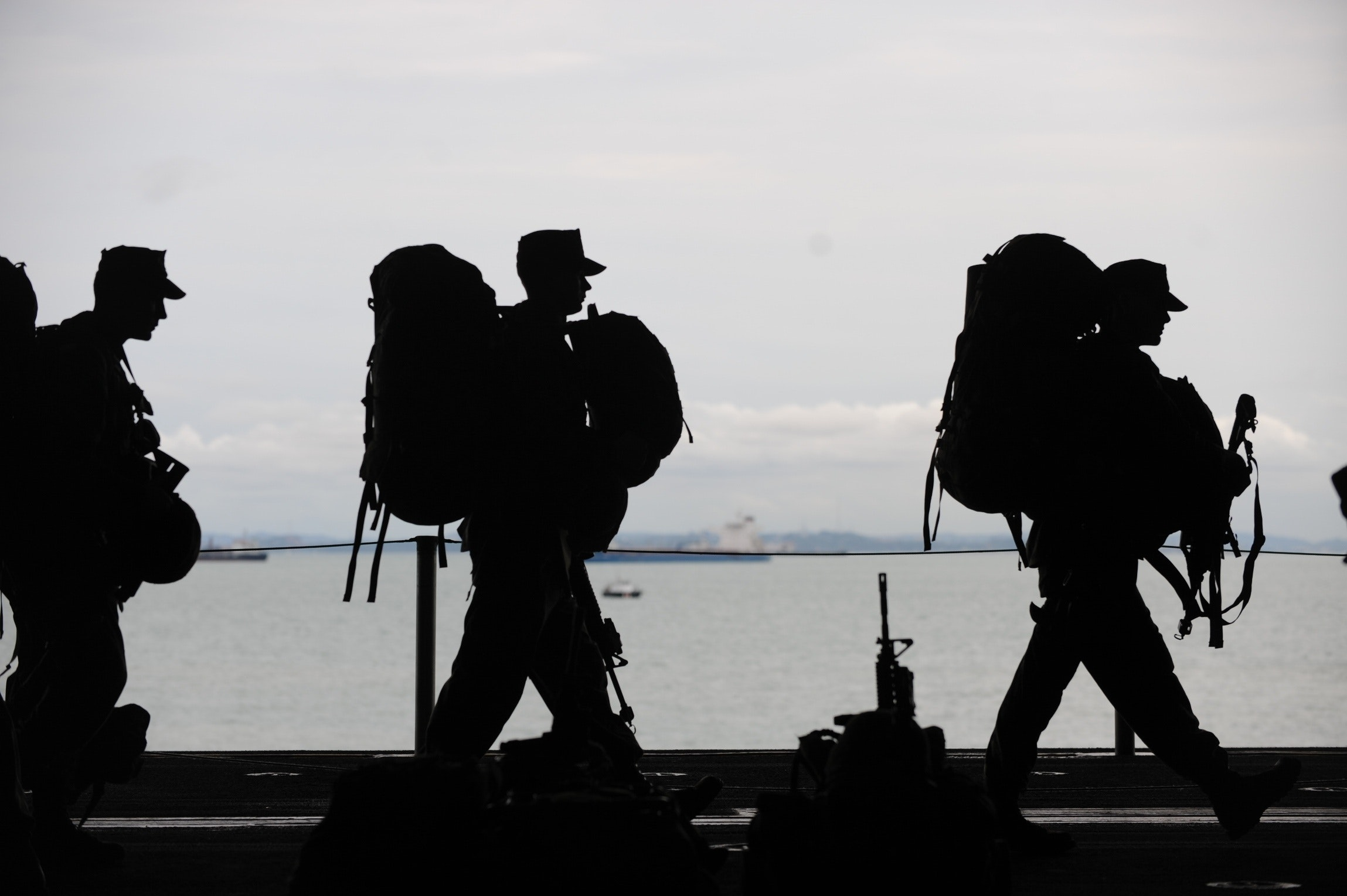 Military workers with travel gear walking in front of water