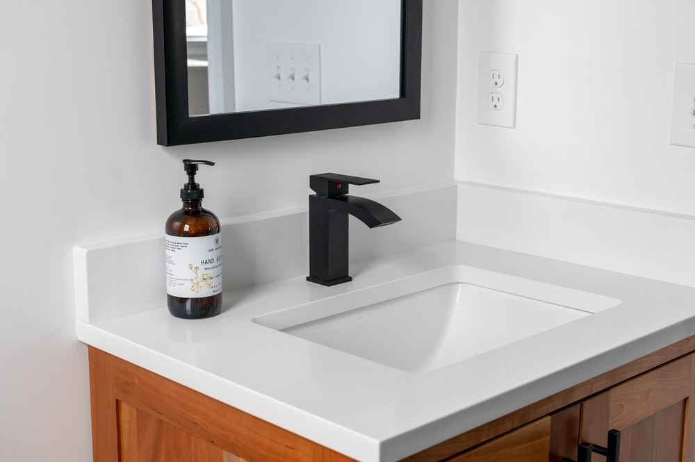 white and black labeled bottle on white ceramic sink