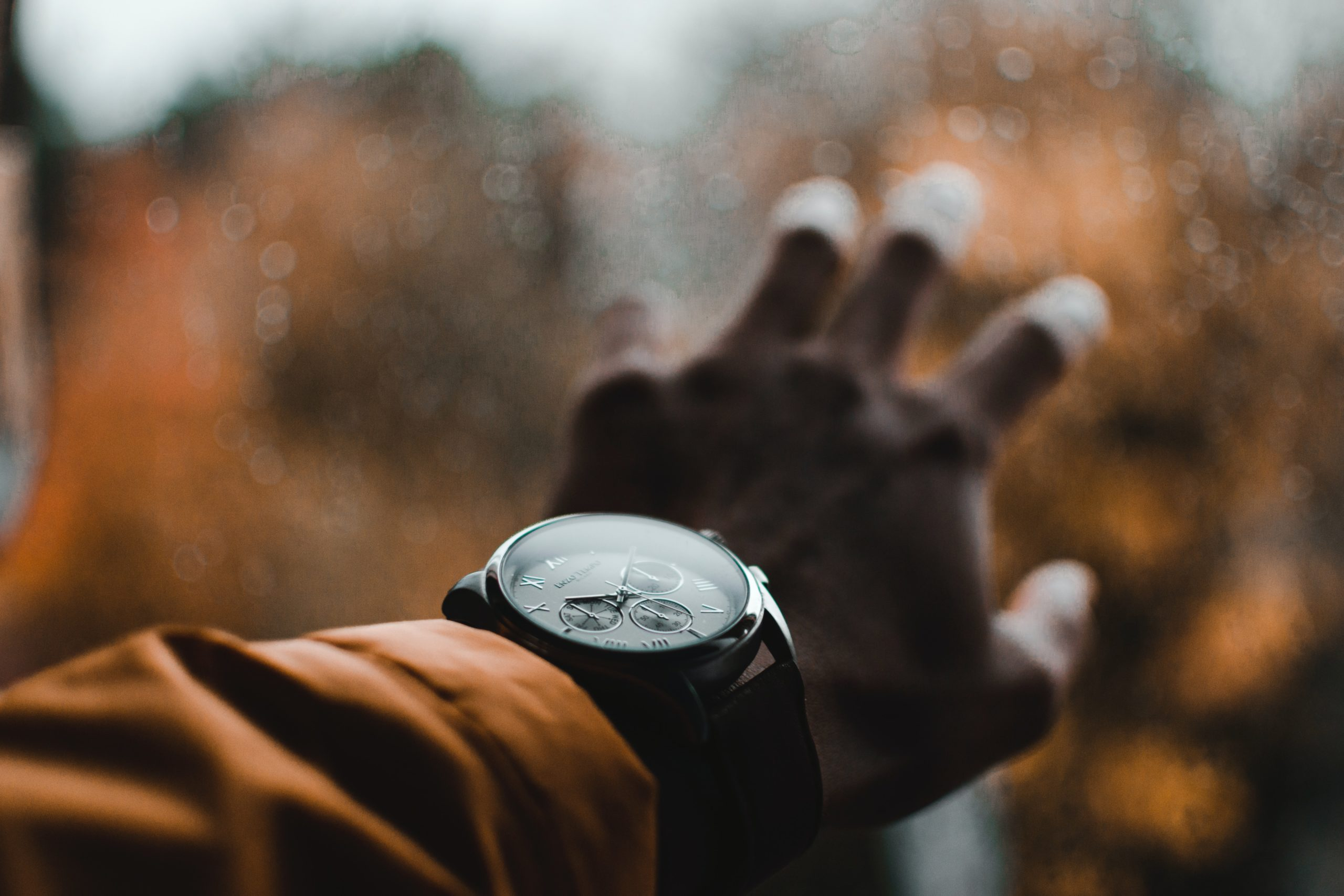 man wearing a large watch with yellow jacket holding his hand against a window in the fall