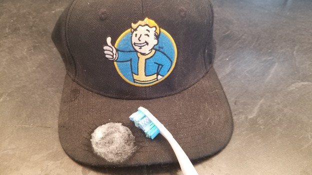 tooth brush spot cleaning a black baseball cap
