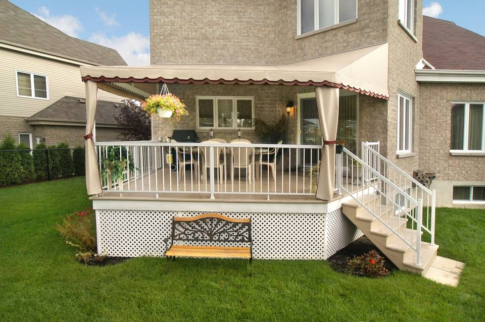 Backyard deck covered with beige sunshade