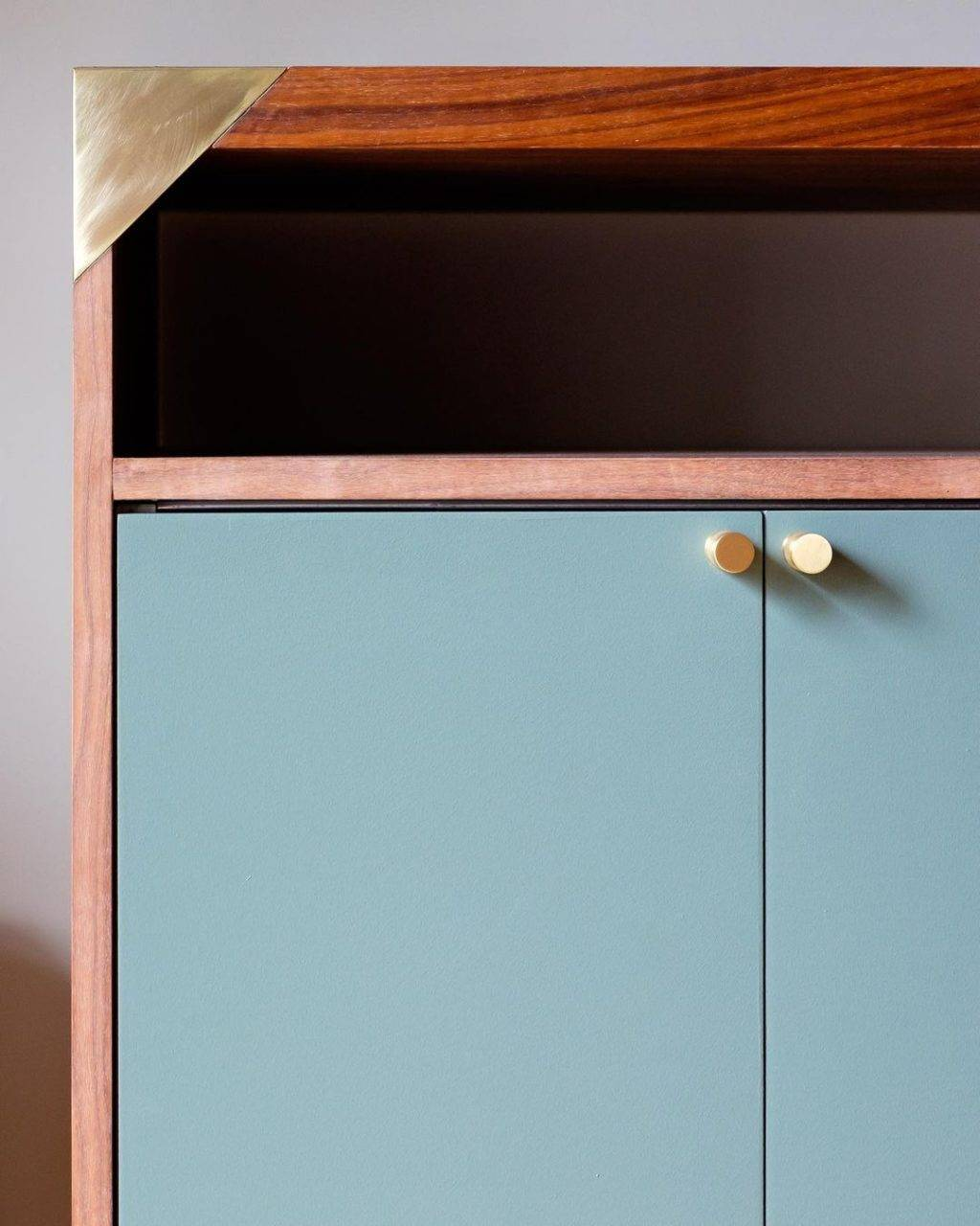 turquoise and wood cabinet with gold knob hardware
