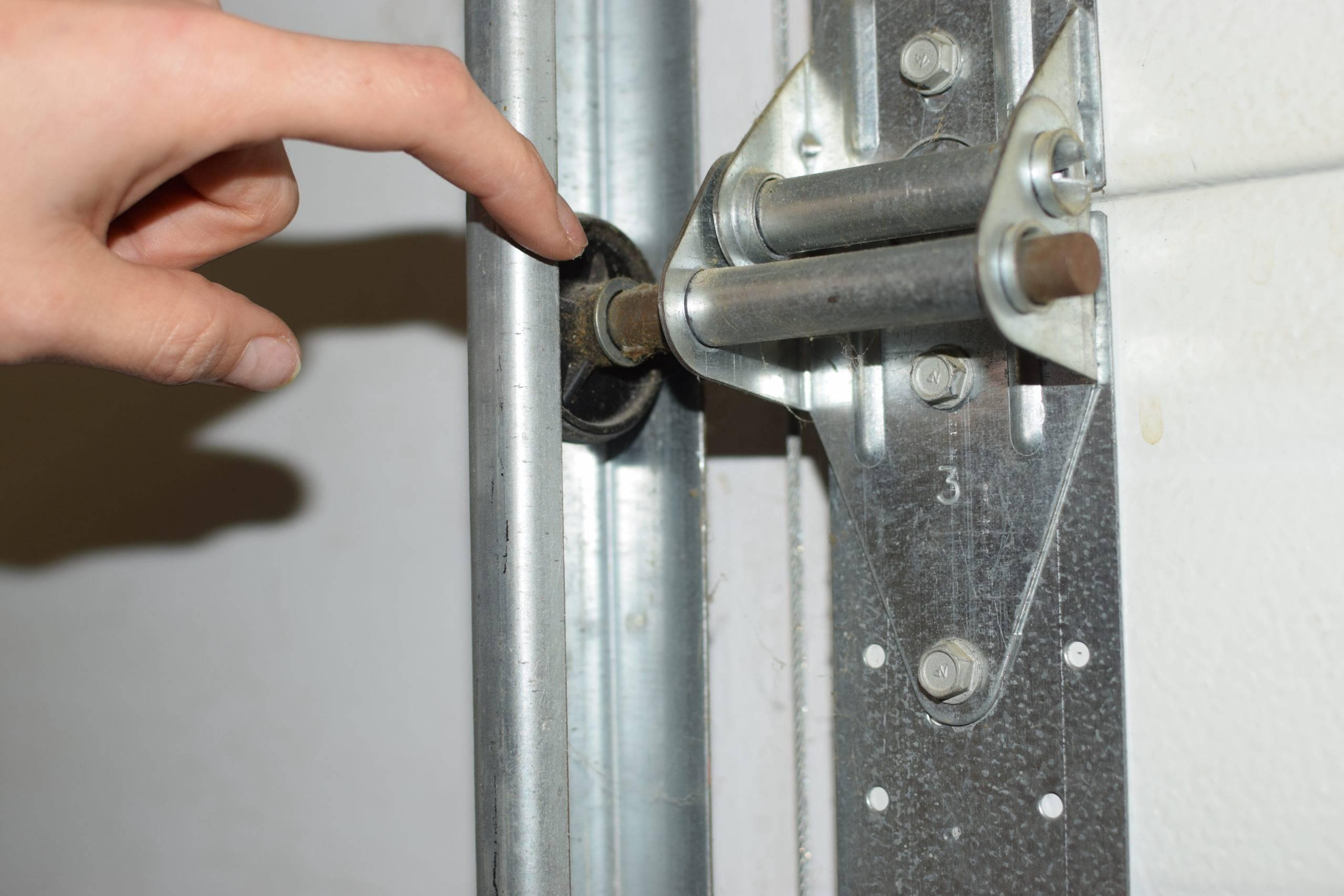 Finger pointing at garage door rollers