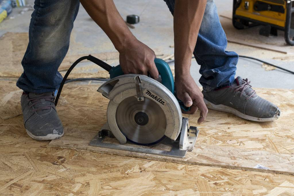 A worker uses a circular saw to cut a piece of flooring