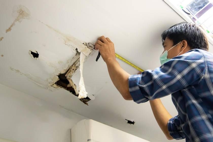 Man checking damage for repair