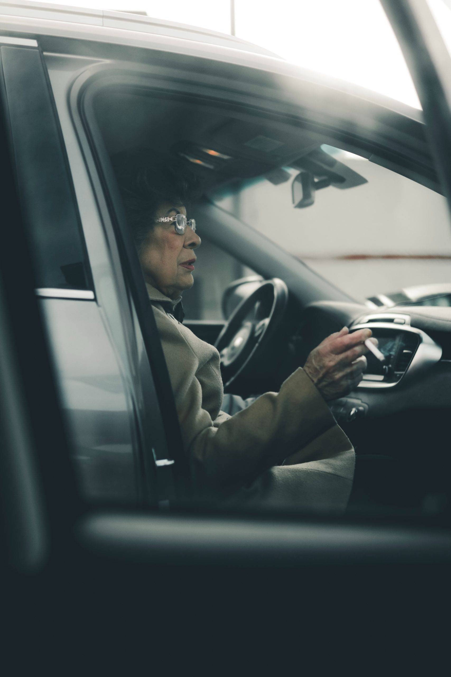 Old woman with cigarette sitting in a parked car