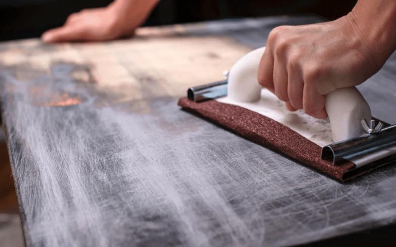 manual hand sander used on wood table
