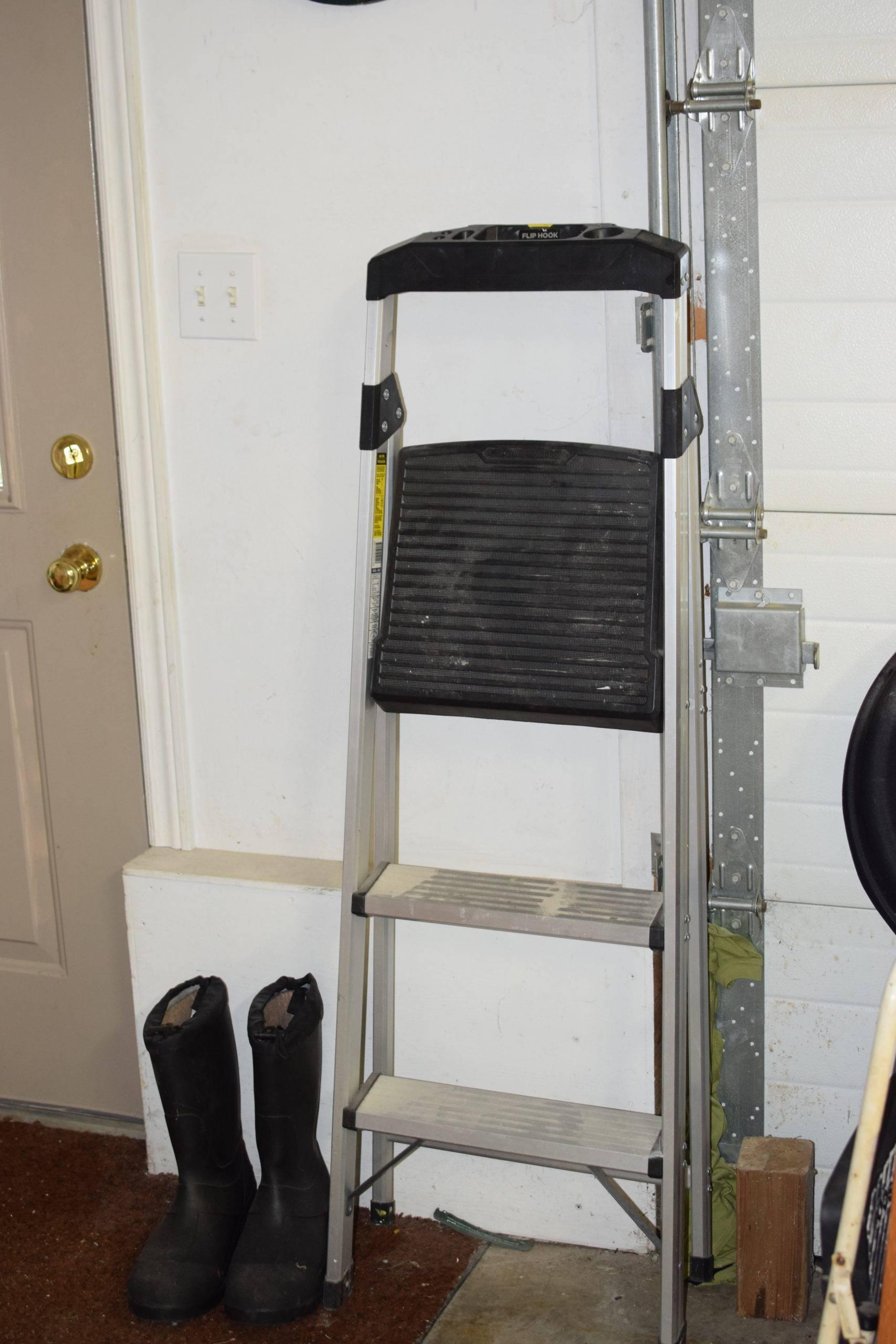 Step up ladder behind black working boots