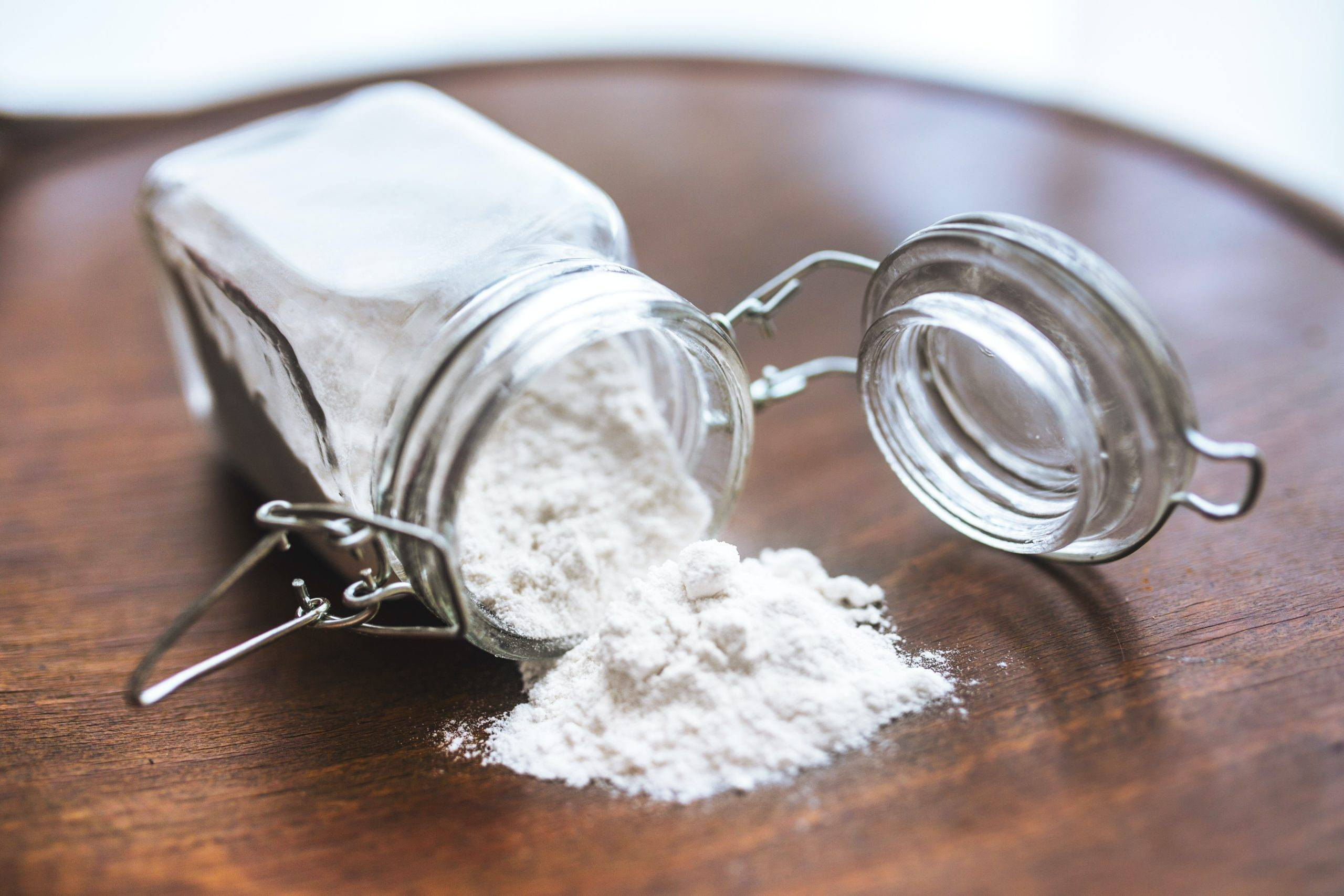 White powder scattered on a table from jar