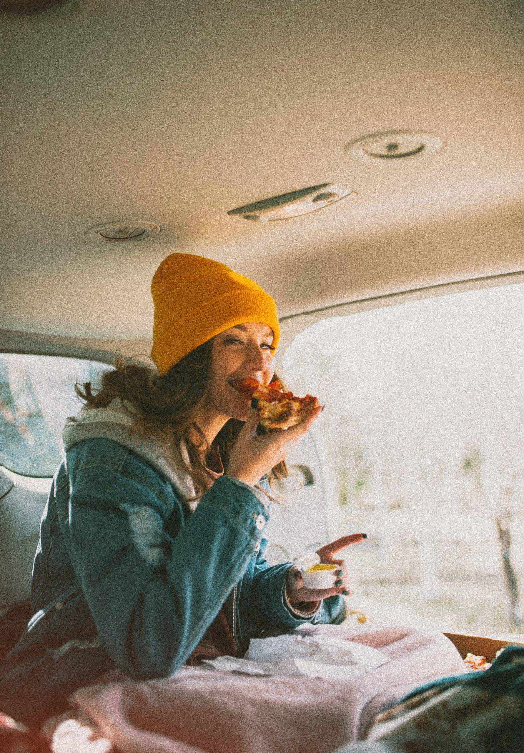 Woman in yellow beanie eating pizza in the car