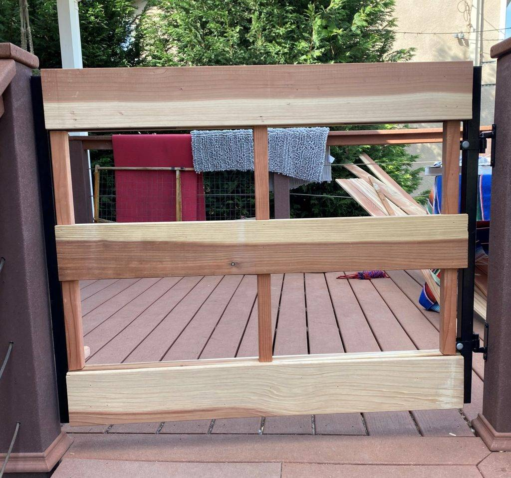 Vertical wood is attached to a metal deck gate frame