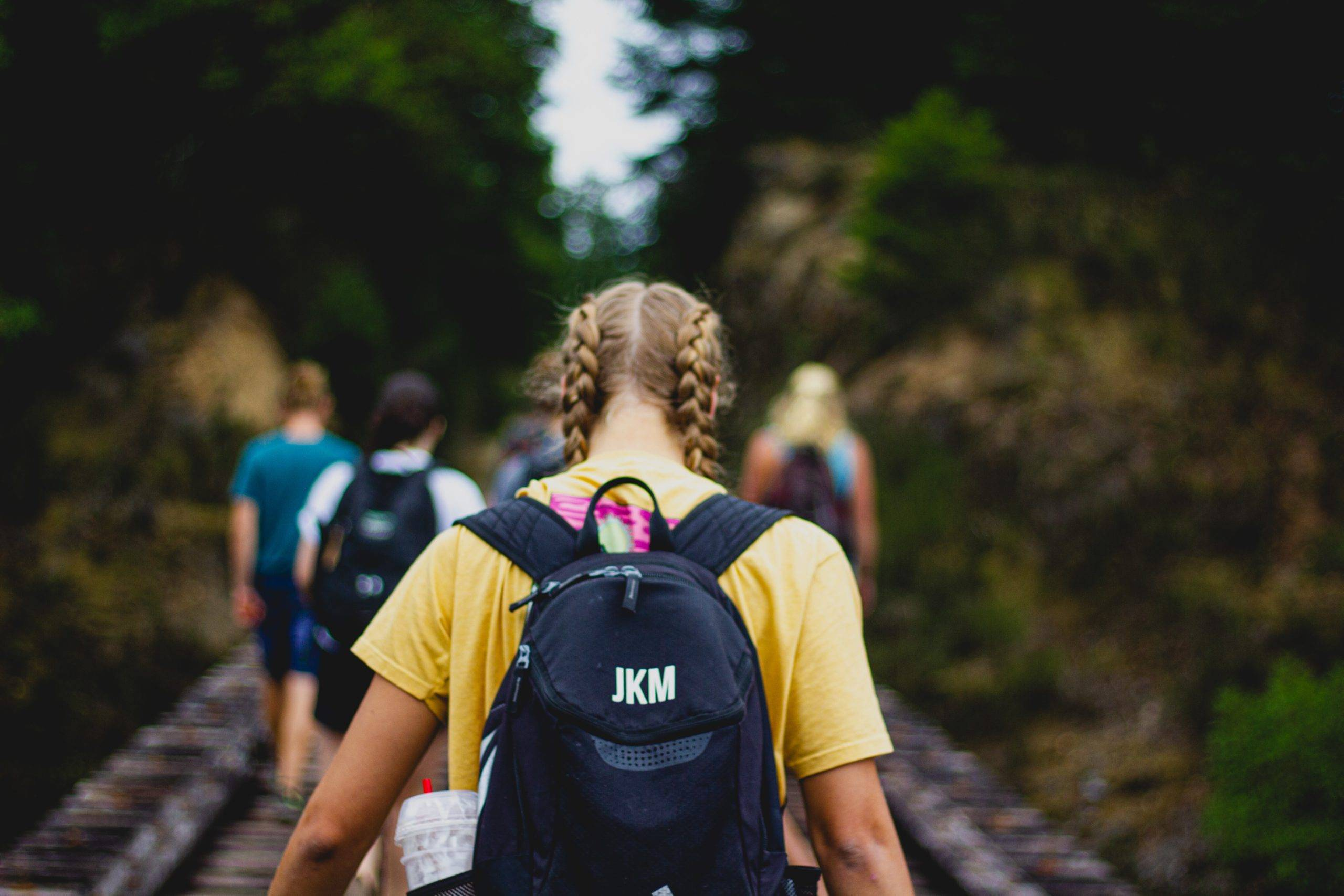 Girl with braided pigtails and black backpack