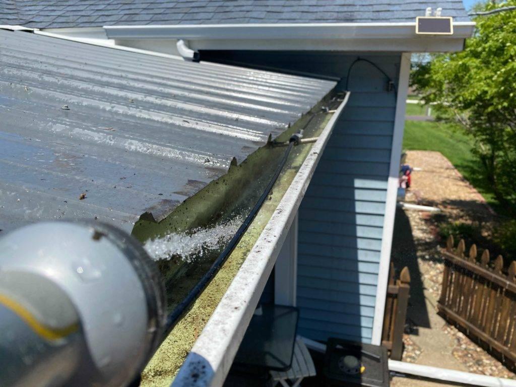 Water Hose Spraying Water in Gutter