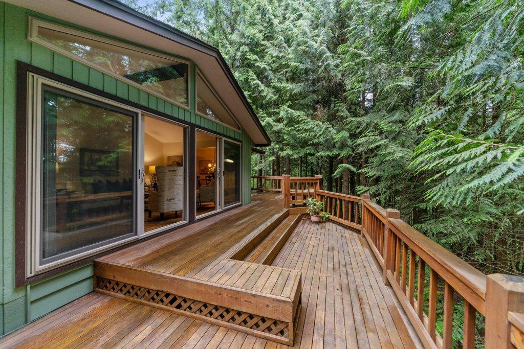 wooden deck on back of cabin in the woods
