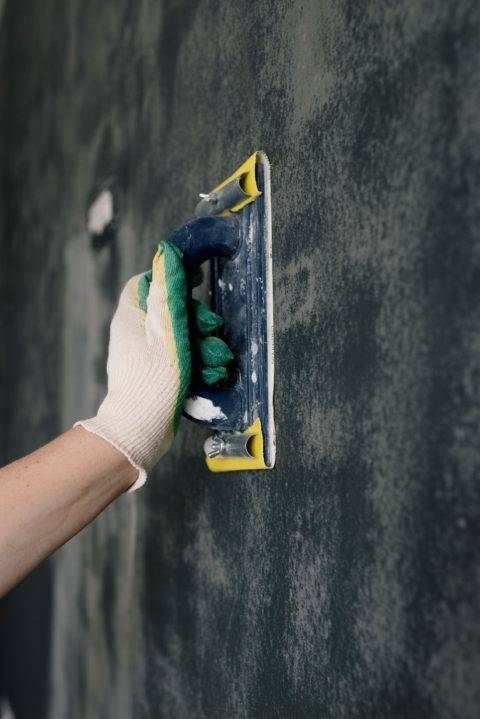 sanding a wall with a hand sander