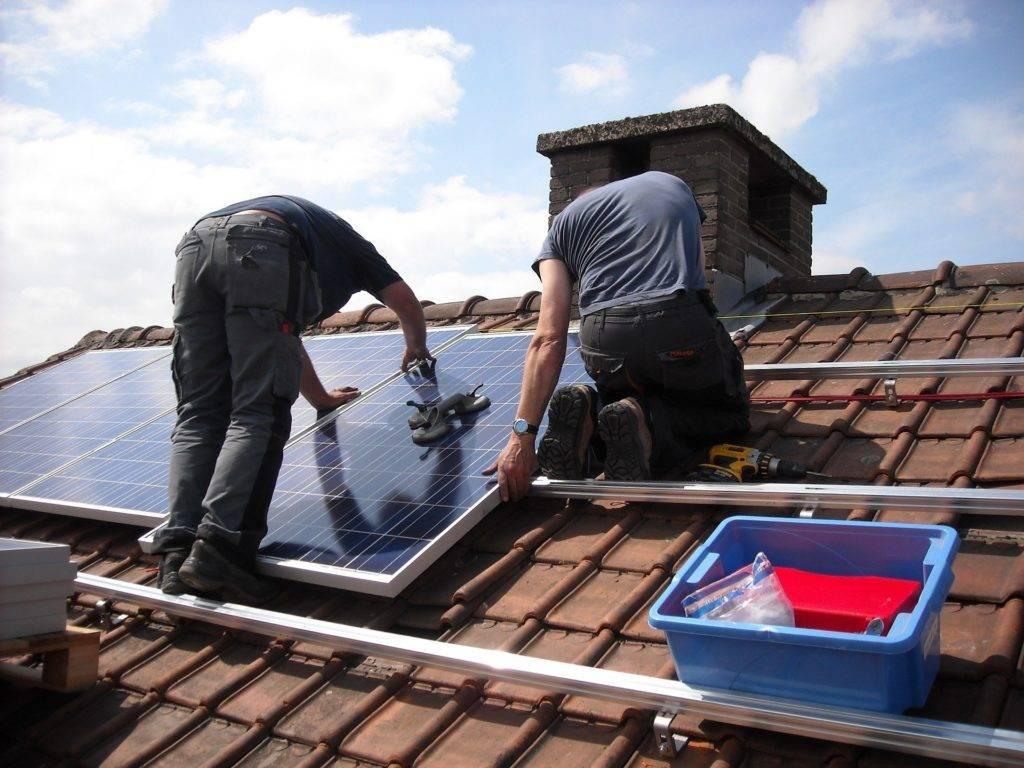 men installing solar panels onto a roof