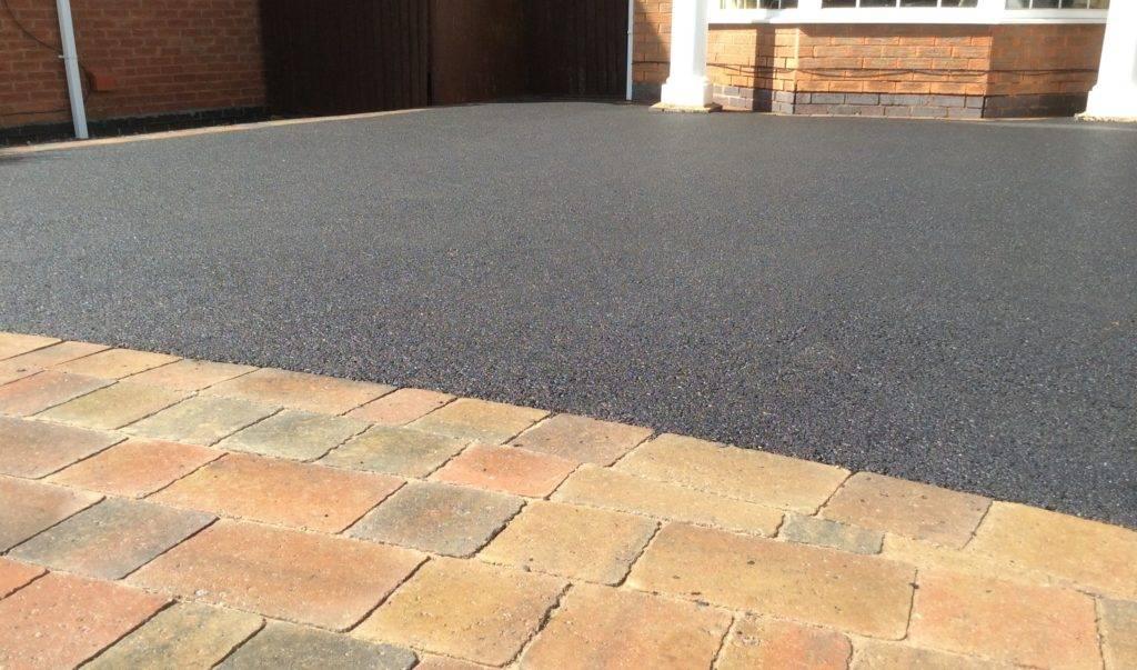 asphalt driveway with brick surrounding