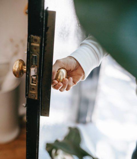 person using door knob to open door into home