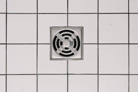 shower drain on white tile floor