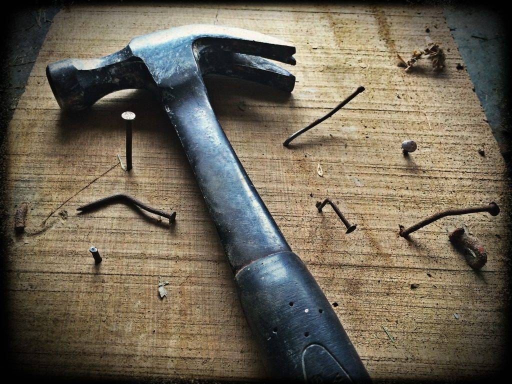 hammer with nails on a board