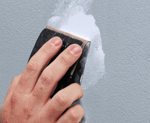 sanding joint compound applied to drywall hole