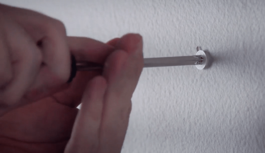 screwdriver being used to remove a drywall anchor