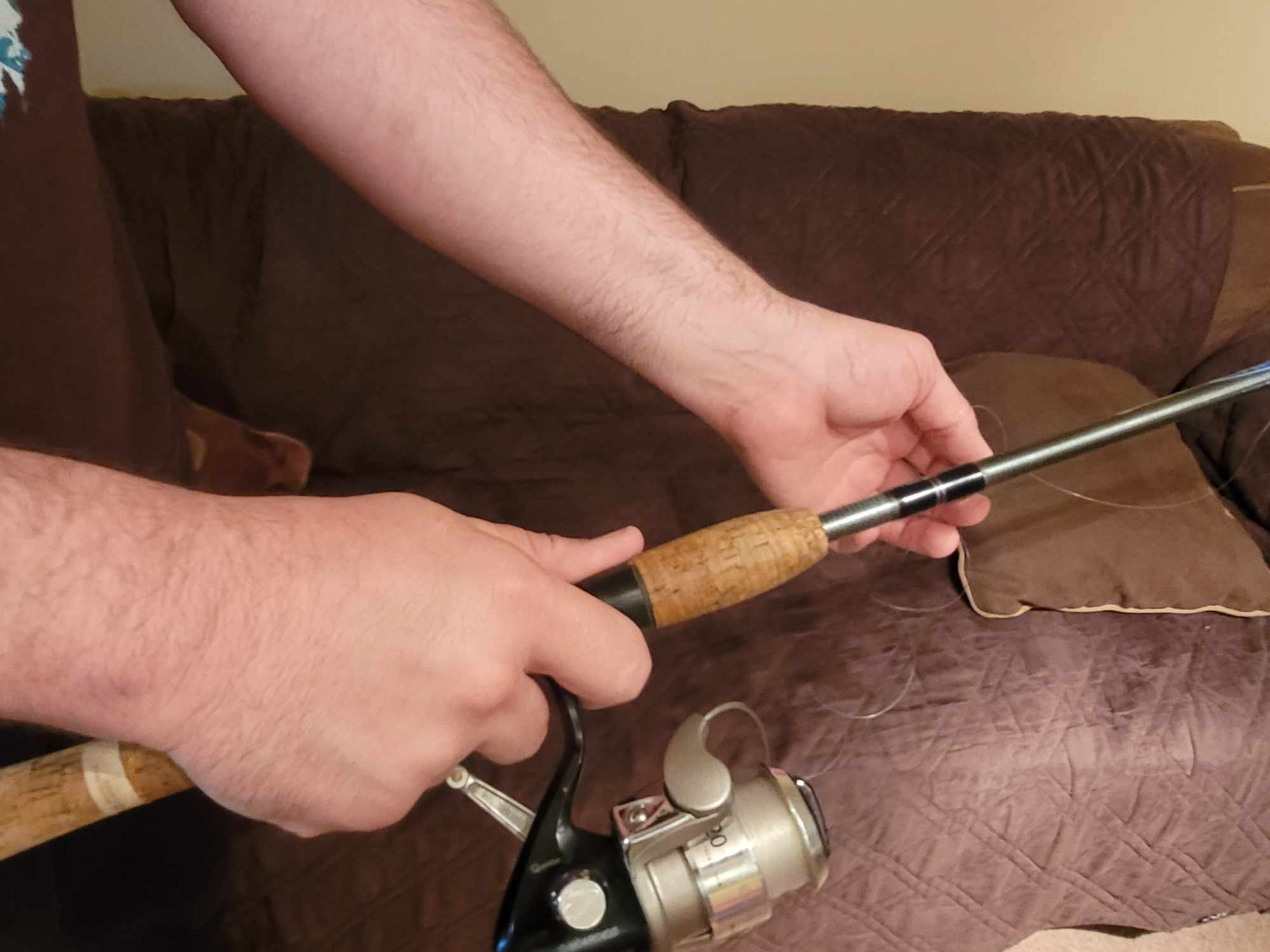 two hands holding spinning reel