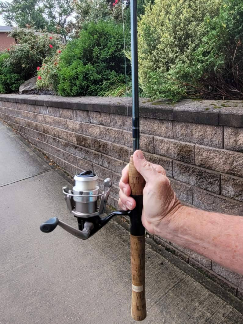 hand holding spinning reel fishing rod vertically