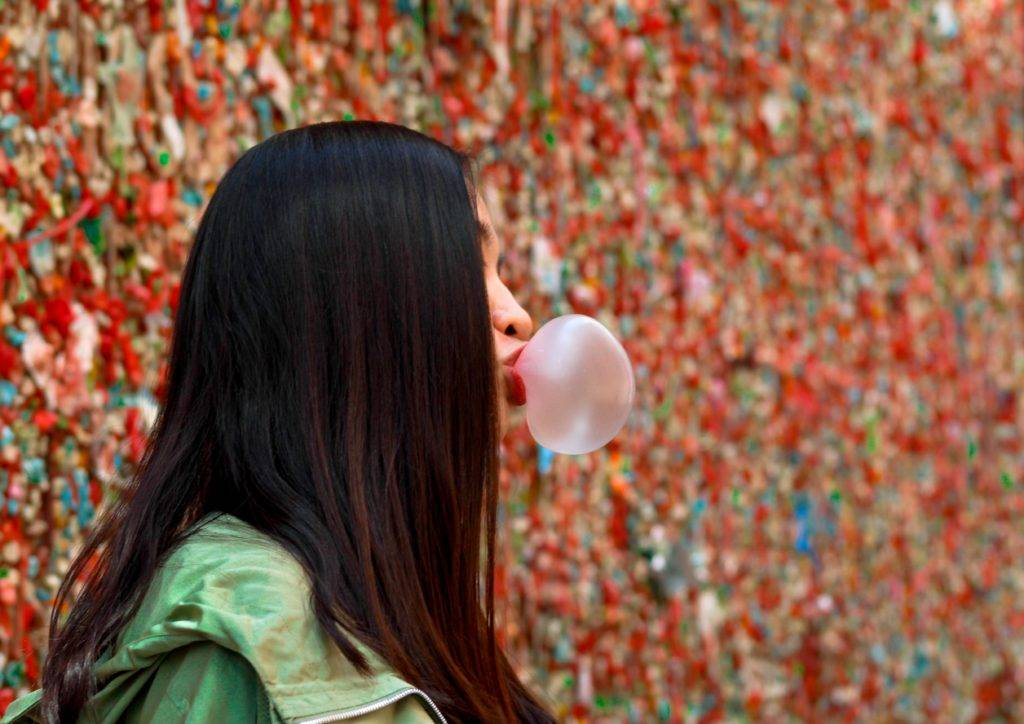 girl in front of a gum wall blowing a bubble