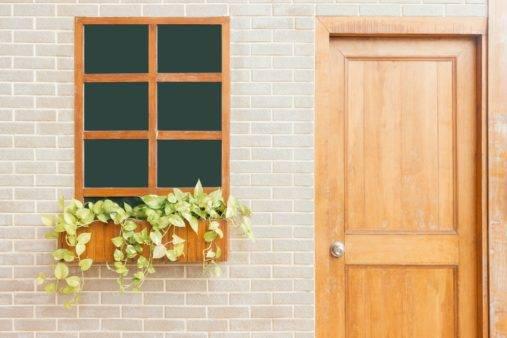 wooden front door next to window with flowers in planter box